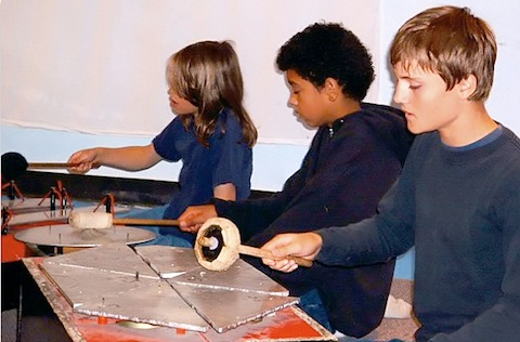 Fifth graders experiment with musical rhythms on a version of the gamelon, a traditional musical instrument from Bali.